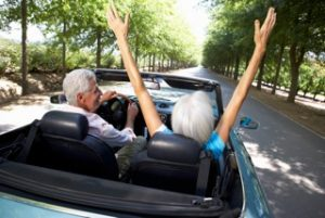 senior couple riding down a road in a convertible, woman in passenger seat has her arms stretched out high