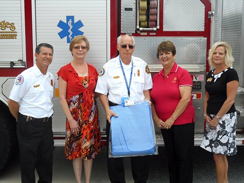 The Villages Insurance team and emergency responders standing in front of a fire truck