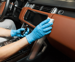 Gloved hands cleaning dashboard of car