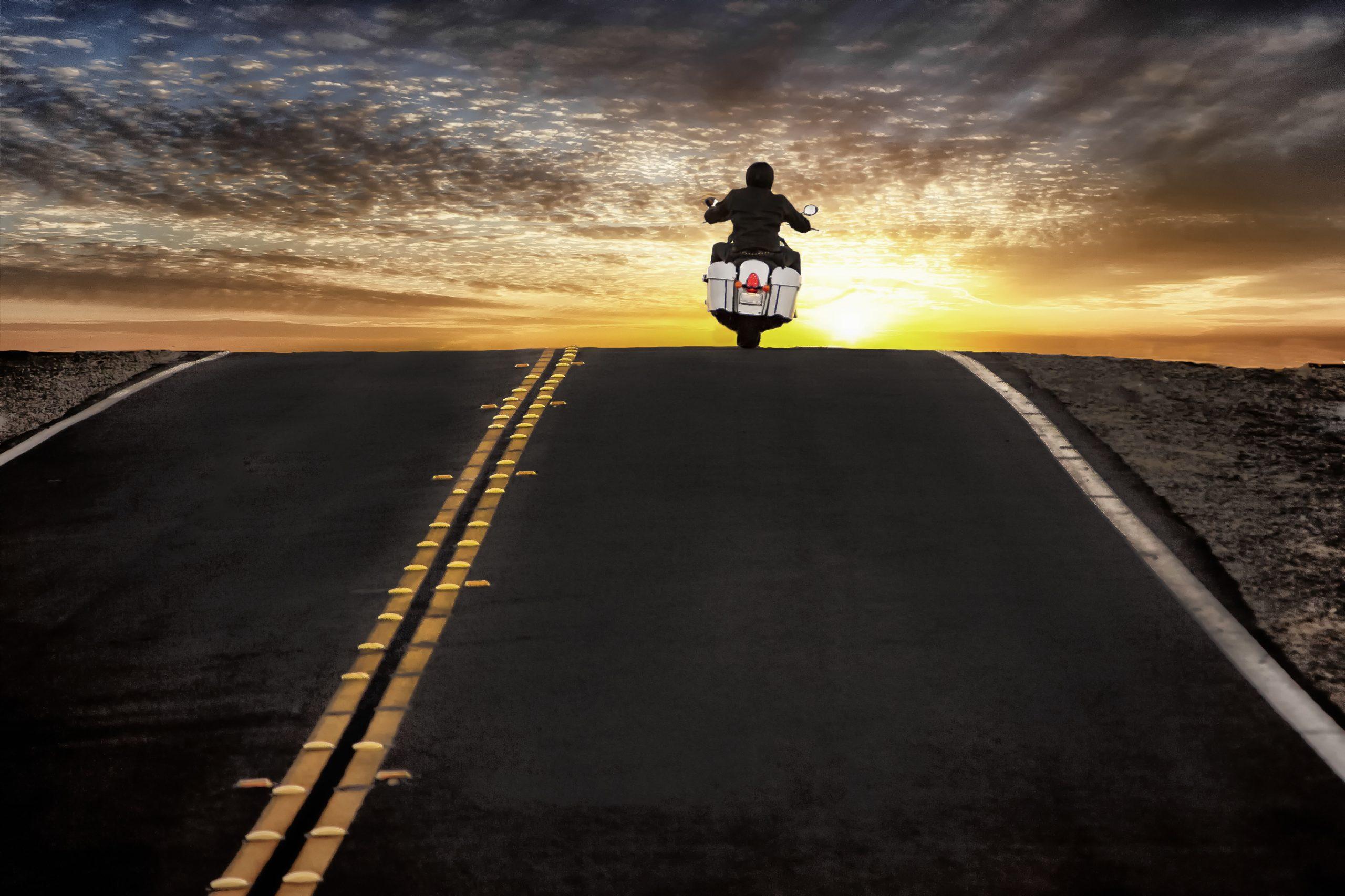Motorcycle rider on street riding toward sunset sky