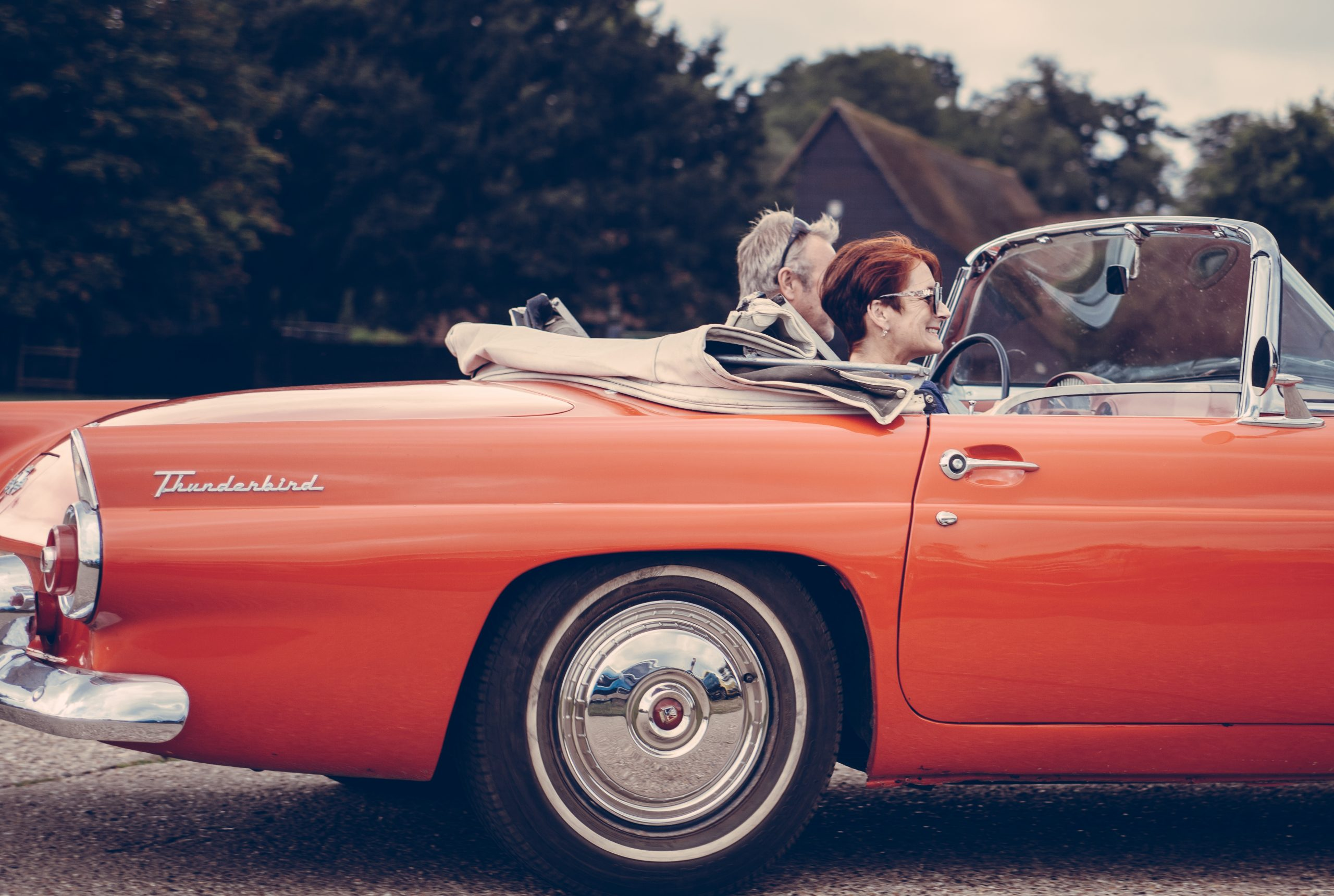 red classic car driven by couple