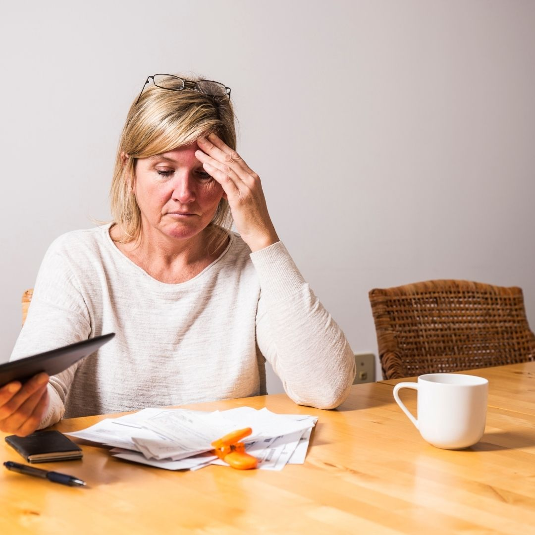 Mature woman distressed over stack of bills