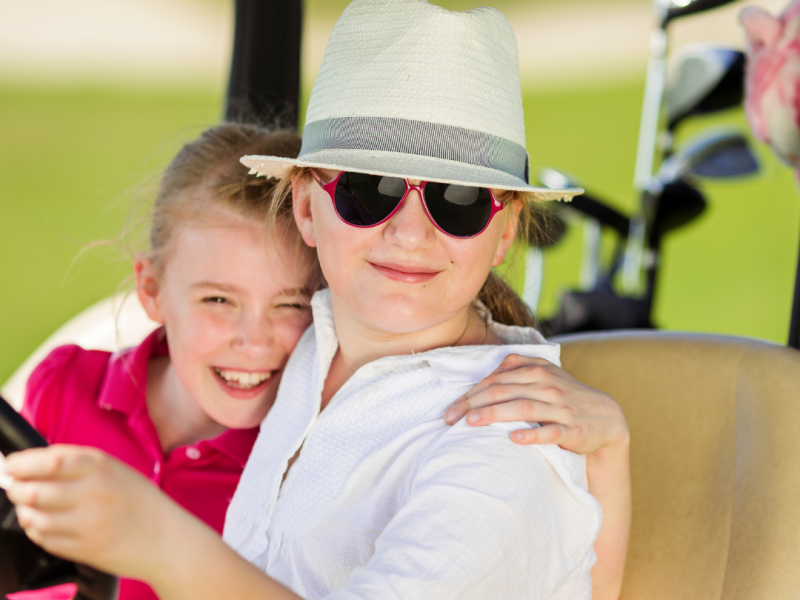 Two young girls sitting in golf cart